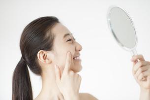 手鏡を見て微笑む女性の写真素材 [FYI02970948]