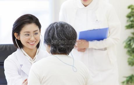 患者に聴診器をあてる女性医師の写真素材 [FYI02970949]