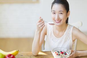 シリアルを食べる笑顔の女性の写真素材 [FYI02970951]