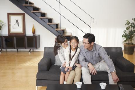 ソファーでくつろぐ3人家族の写真素材 [FYI02970952]