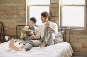 ベッドの上で本を読みながら笑い合う男性と女性の写真素材 [FYI02970953]
