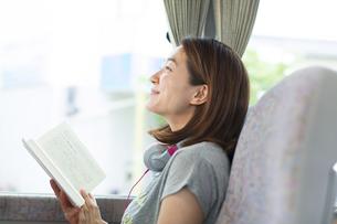 バスの中で読書中に微笑む女性の写真素材 [FYI02970954]