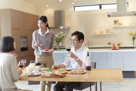 ホームパーティでワインと食事を楽しむ男女の写真素材 [FYI02970963]