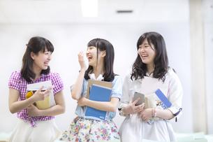 教室で教材を持って会話する女子学生たちの写真素材 [FYI02970968]