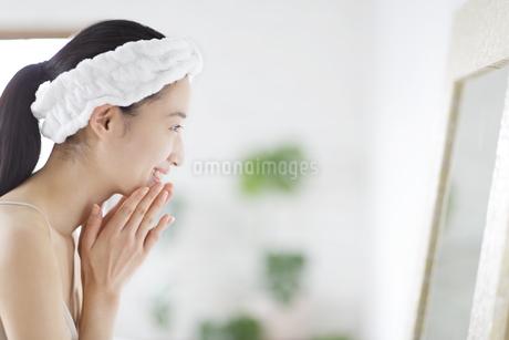 鏡の前でスキンケアをする微笑む女性の横顔の写真素材 [FYI02970969]