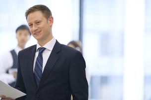 オフィスビルのロビーで資料を持って微笑むビジネス男性の写真素材 [FYI02970974]