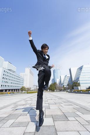 こぶしを上げてジャンプするビジネス男性の写真素材 [FYI02970977]