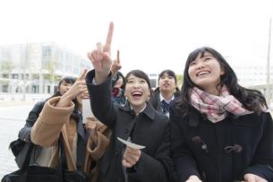 受験番号票を手に番号を確認している女子高校生たちの写真素材 [FYI02970979]