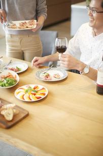 ワインを手に笑う男性とオードブルをくばる女性の写真素材 [FYI02970980]