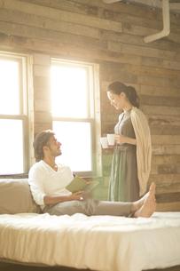 ベッドの上にいる男性にカップを手渡す女性の写真素材 [FYI02970982]
