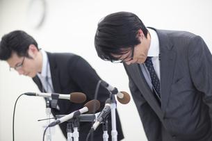 謝罪会見で頭を下げるビジネス男性2人の写真素材 [FYI02970983]