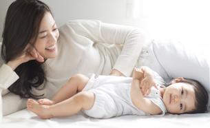 ベッドの上で赤ちゃんをあやす女性の写真素材 [FYI02970985]