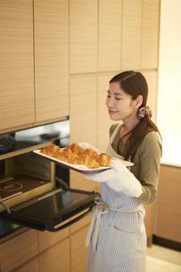 焼いたクロワッサンの匂いをかぐ主婦の写真素材 [FYI02970988]