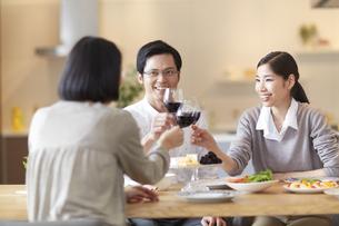 ホームパーティでワインを手に乾杯する男女三人の写真素材 [FYI02970989]