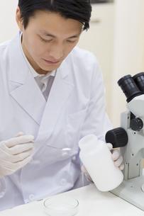 薬さじを使って研究をしている男性研究員の写真素材 [FYI02970990]