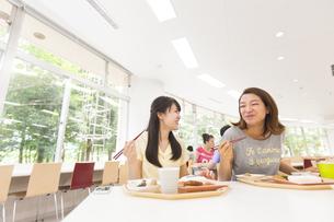 学食で食べながら笑う学生たちの写真素材 [FYI02970992]