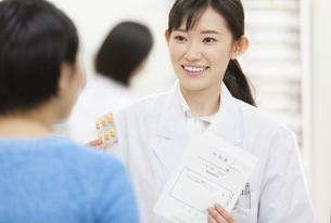 薬の説明をする女性薬剤師と患者の写真素材 [FYI02970993]