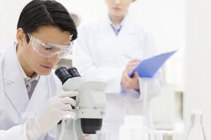 顕微鏡を覗く男性研究員の写真素材 [FYI02970995]