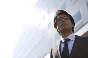 ビルの前で遠くを見るビジネス男性の写真素材 [FYI02970997]