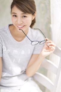 カーテンの傍で椅子に座り片手に眼鏡を持って微笑む女性の写真素材 [FYI02971017]