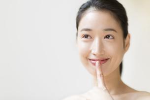 唇に指をあて微笑む女性の写真素材 [FYI02971019]