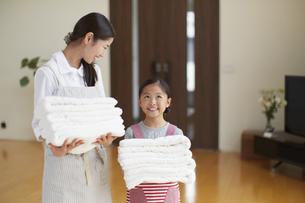 タオルを持って笑う母親とおどけた表情をする女の子の写真素材 [FYI02971023]