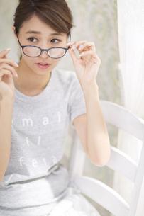 カーテンの傍で椅子に座って眼鏡を掛ける女性の写真素材 [FYI02971024]