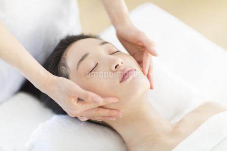 仰向けで顔をマッサージされている女性の写真素材 [FYI02971025]