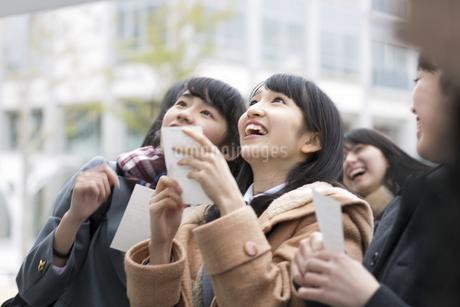 受験番号票を手に番号を確認している女子高校生たちの写真素材 [FYI02971028]