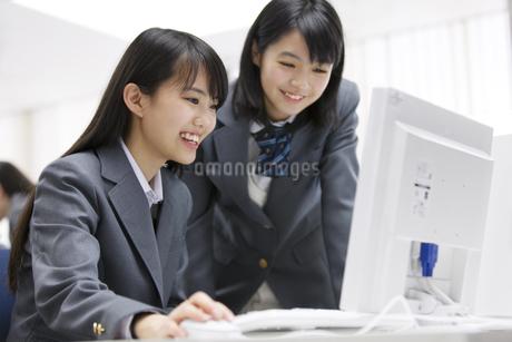 パソコン教室でモニターに向かって微笑む2人の女子高校生の写真素材 [FYI02971033]