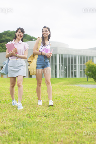 笑いながら芝を歩く2人の女子学生の写真素材 [FYI02971035]