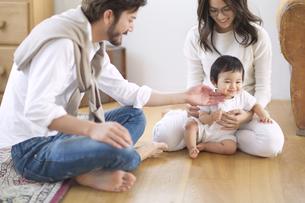 赤ちゃんをあやす若い夫婦の写真素材 [FYI02971037]