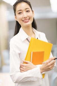 オフィスでファイルを手に微笑むビジネス女性の写真素材 [FYI02971046]