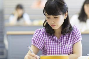 講義でノートをとる女子学生の写真素材 [FYI02971048]