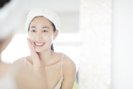 鏡の前でスキンケアをする微笑む女性の写真素材 [FYI02971050]