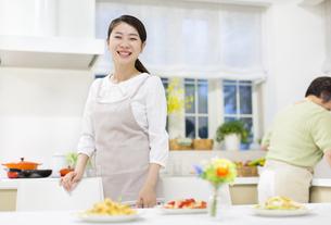 食卓の料理の前で笑顔の若い奥さんの写真素材 [FYI02971052]