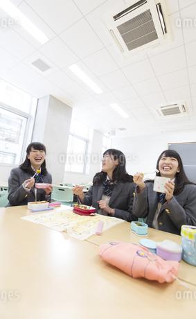 教室でお弁当を食べながら笑う3人の女子高校生の写真素材 [FYI02971053]