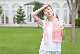ペットボトルを持って額に腕をあてる女性の写真素材 [FYI02971054]