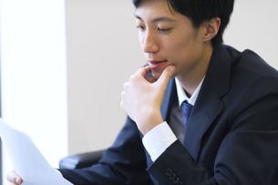顎に手をあて考えるビジネス男性の写真素材 [FYI02971060]