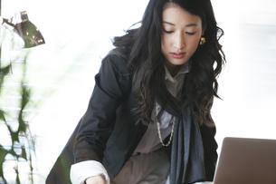 オフィスのデスクの資料を取ろうとするビジネス女性の写真素材 [FYI02971083]