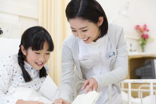 病室で絵本を楽しむ女の子と女性看護師の写真素材 [FYI02971084]