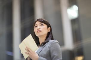 手帳を持ち上を見上げるビジネス女性の写真素材 [FYI02971085]