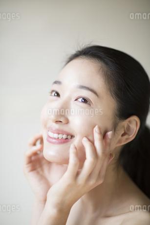 頬に両手を添えて上を見上げる女性の写真素材 [FYI02971086]