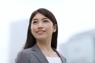 オフィスビルを背景に微笑むビジネス女性の写真素材 [FYI02971088]