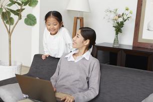 ソファーでノートパソコンを見る母と子の写真素材 [FYI02971089]