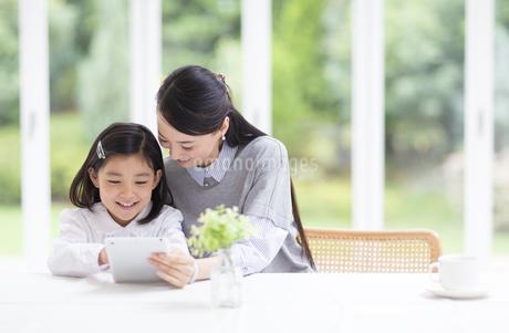 母の持つタブレットPCにタップする女の子の写真素材 [FYI02971094]