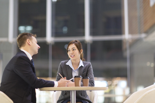 オフィスビルのロビーで打ち合せをするビジネス男女の写真素材 [FYI02971115]