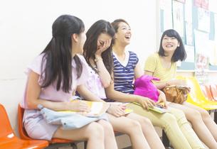 廊下の椅子に並んで座って笑い合う女子学生たちの写真素材 [FYI02971117]