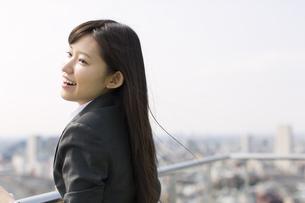屋上で遠くを見ながら微笑むビジネス女性の写真素材 [FYI02971119]