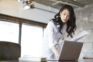 オフィスのデスクでパソコンを見るビジネス女性の写真素材 [FYI02971121]